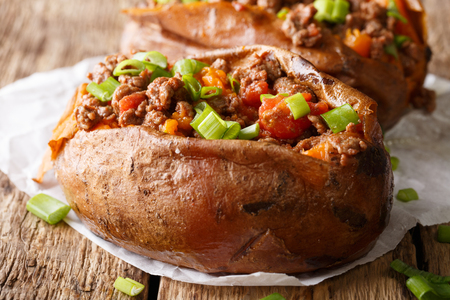 Baked sweet potatoes stuffed with ground beef with tomatoes and onions macro on paper on a table. horizontal  Stock Photo