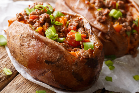 Baked whole sweet potatoes stuffed with ground beef and onions macro on a table. horizontal