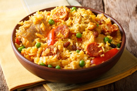 Delicious food: Arroz Valenciana with rice, meat, sausage, raisins and vegetables close-up in a bowl on the table. horizontal