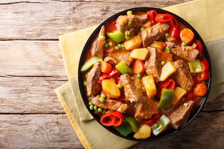 Asian food: Stewed beef with potatoes, peppers, peas, tomatoes and carrots close-up on a plate on the table.