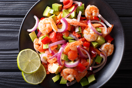 Spicy shrimp ceviche with vegetable salsa close-up on a plate on a table. horizontal top view from above