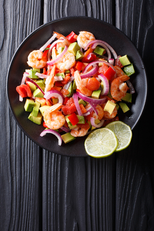 Delicious ceviche of shrimp with vegetables, spices and lime close up on a plate on the table. Vertical top view from above  Stock Photo