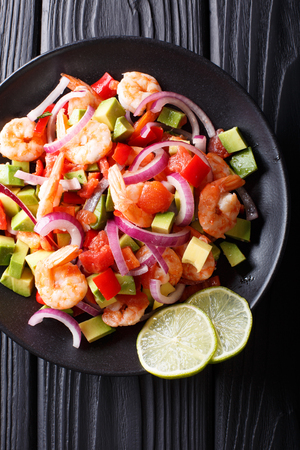 Spicy shrimp ceviche with vegetable salsa close-up on a plate on a table. Vertical top view from above  Stock Photo