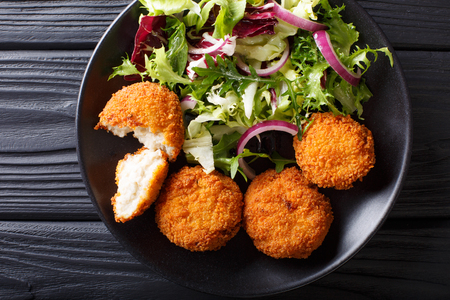 Homemade codfish cake and fresh salad closeup on a plate on the table. Horizontal top view from above