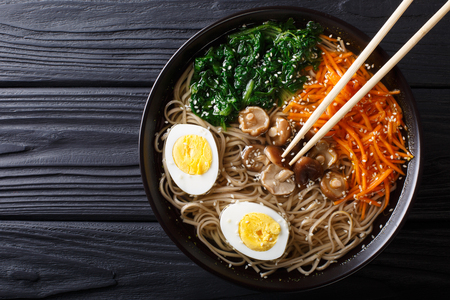 Asian Soba soup with vegetables, mushrooms, egg and sesame seeds close up in a bowl. horizontal top view from above