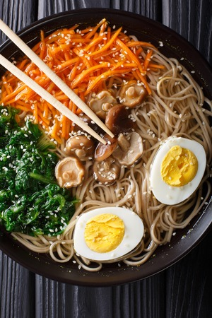 Soba noodles soup with vegetables, shiitake mushrooms, egg and sesame close-up in a bowl. Vertical top view from above