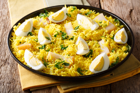Kedgeree tasty food with rice, fish, boiled eggs, cilantro close-up on a plate on a table. horizontal