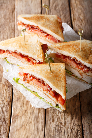 Club sandwiches with roasted turkey meat, bacon, tomatoes and lettuce close-up on the table. vertical  Stock Photo