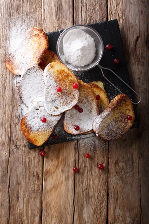 Brazilian sweet Rabanadas toast with powdered sugar and cranberries close-up on the table. Vertical top view from above