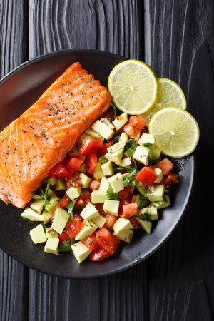 spicy baked salmon steak and fresh vegetable salad close-up on a plate. Vertical top view from above  Stock Photo