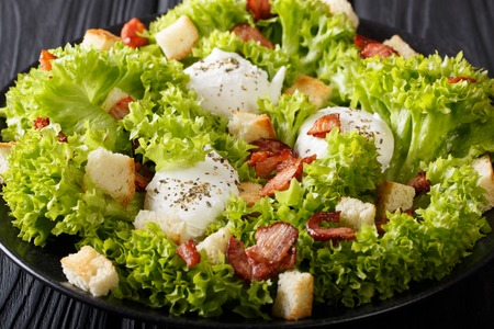 French Lyons Lyonnaise salad with lettuce, croutons and poached eggs close-up on a plate on the table. horizontal Banque d'images