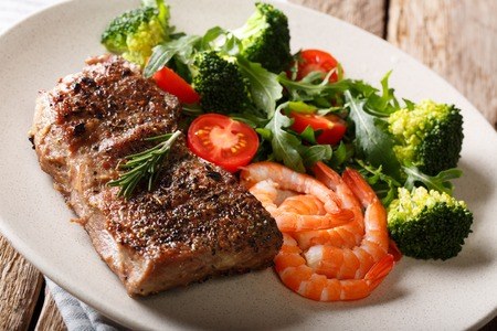 Beef steak with prawns and broccoli, tomatoes, arugula closeup on plate on table. Horizontal. Surf and Turf.