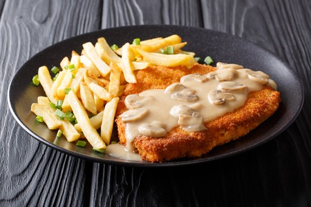 Crispy Fried Pork Chops (Jaeger Schnitzel) with sauce and french fries close-up on a plate. Horizontal  Фото со стока