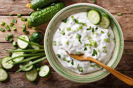 sauce of yogurt with herbs, spices and cucumber close-up in a bowl on the table. raita. horizontal top view from above
