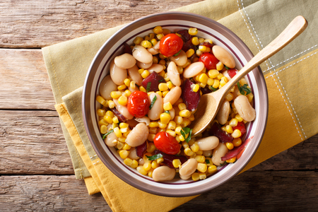 succotash of corn, butter beans, tomatoes and bacon close up in a bowl on the table. horizontal top view from above