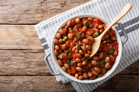 Stewed cranberry beans or borlotti in tomato sauce with herbs close-up in a bowl on the table. horizontal top view from above