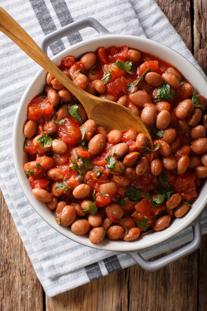 Organic Borlotti beans in tomato sauce with herbs close-up in a bowl on the table. Vertical top view from above Archivio Fotografico