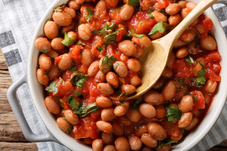 Cranberry beans in tomato sauce with herbs close-up in a bowl on the table. horizontal top view from above Archivio Fotografico