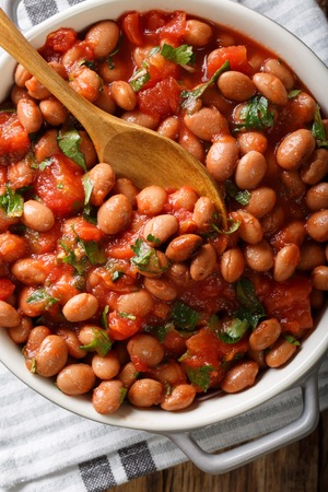 Cranberry beans in tomato sauce with herbs close-up in a bowl on the table. Vertical top view from above