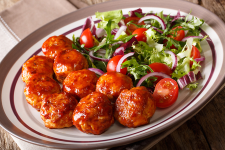 fried meatballs with salad of tomato, lettuce mix and onion close-up on a plate on the table. horizontal