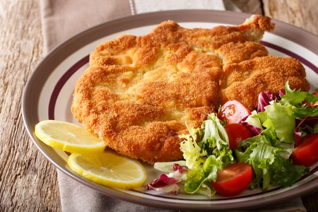 Veal milanese (cotoletta alla milanese) with lemon and fresh vegetable salad close-up on a plate. horizontal