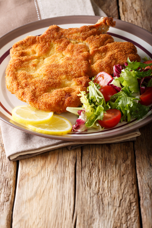 Fried veal cutlet Milanese with lemon and fresh salad of tomatoes and lettuce close-up on a plate on a table. vertical