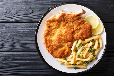 Traditional Italian veal Milanese with lemon and French fries close-up on a plate. horizontal top view from above