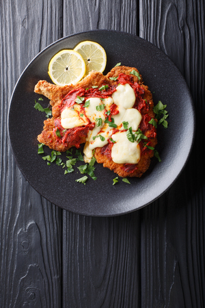 Veal Milanesa Napolitana with mozzarella cheese and tomato sauce close-up on a plate on a table. Vertical top view from above