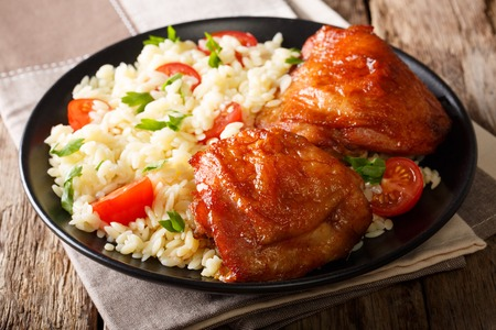 Portion of fried chicken thighs with garnish of rice with vegetables on a plate close-up. horizontal