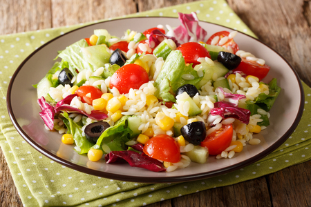 Tasty salad of fresh vegetables, rice and lettuce close-up on a plate on a table. horizontal