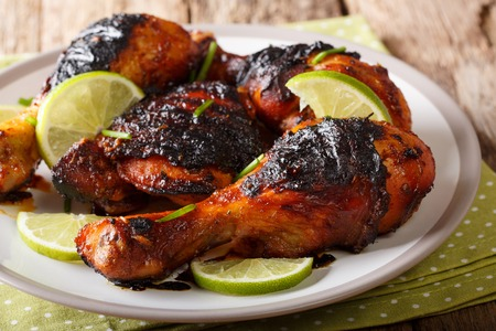 Caribbean grilled chicken drumstick with lime and onions closeup on a plate on a table. horizontal