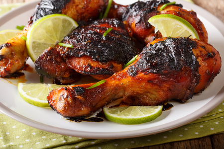 Jamaican food: jerk chicken drumstick with lime closeup on a plate on the table. horizontal