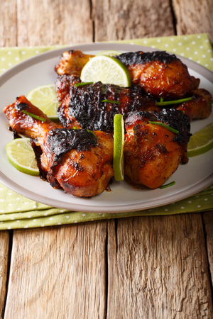 Grilled jerk chicken drumstick with lime and onions closeup on a plate on a table. vertical  Stock Photo