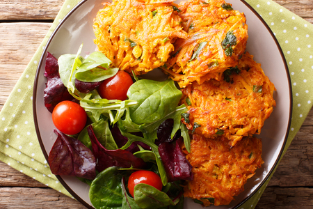 Freshly made crispy fritters from sweet potato and fresh vegetable salad on a plate close-up. horizontal top view from above
