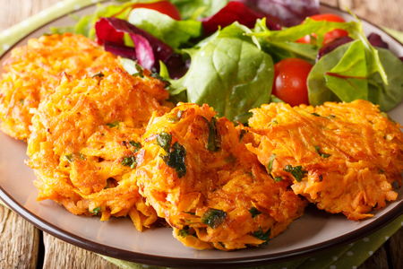 Homemade fritters of sweet potatoes and fresh mix of salad on a plate close-up. horizontal