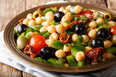 Vegan salad balela with chickpeas, tomatoes, onions, olives and herbs close-up on a plate. horizontal