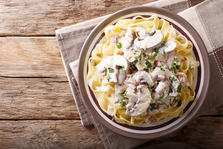 Fettuccine with traditional Italian creamy Boscaiola sauce closeup on a plate on a table. horizontal top view from above  Stock Photo