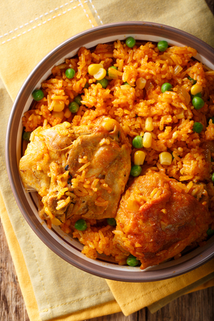 Galinhada is the Brazilian version of arroz con pollo chicken and rice close-up on a plate on a table. Vertical top view from above Foto de archivo - 99424178