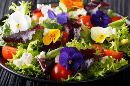 Delicious salad of edible flowers with lettuce, tomatoes and feta close-up on the table. horizontal