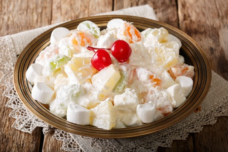 fruit salad from pineapple, oranges, grapes and coconut with marshmallow and vanilla yogurt close-up on a plate. horizontal