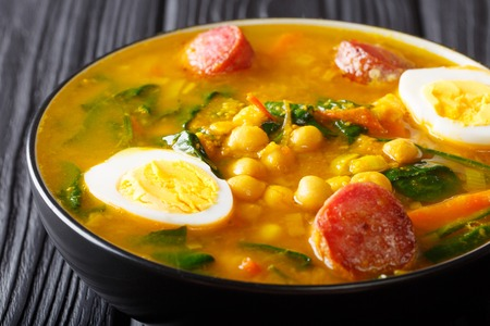 Spicy soup with spinach, chickpeas, chorizo sausages, boiled eggs close-up in a bowl on the table. horizontal
