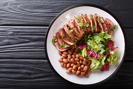 Serving grilled beef steak with fresh salad and beans close-up on a plate on a table. horizontal top view from above