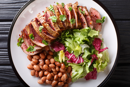 Grilled chopped beef steak with fresh salad and beans close-up on a plate. horizontal top view from above