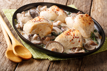 Spicy chicken fillet with a mix of wild mushrooms and spinach in a creamy sauce close-up on a plate on a table. horizontal