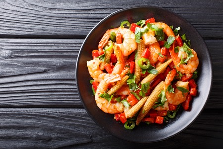 Portion of spicy shrimp with pepper, garlic, corn cob and herbs close-up on a plate. horizontal top view from above Stock Photo