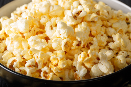 Tasty popcorn with cheese cheddar and parmesan in a bowl macro on the table. horizontal