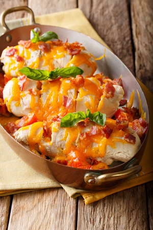 Homemade chicken breast with bacon, tomatoes, cheddar cheese and basil close-up in a copper frying pan. vertical