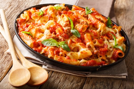 Casserole ziti pasta with minced meat, tomatoes, herbs and cheese close-up on a plate. horizontal
