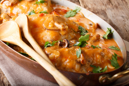 Classic French chicken chasseur with mushrooms and tomatoes in spicy sauce close-up on the table. horizontal  Stock Photo