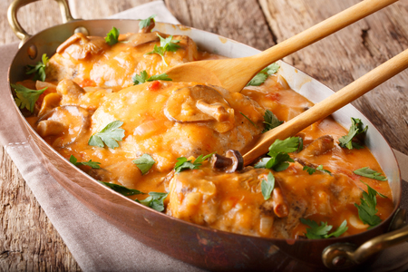 Home French chicken chasseur with mushrooms and tomatoes close-up on the table. horizontal